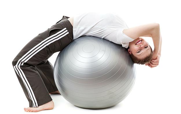 kobieta wykonująca ćwiczenia na piłce rehabilitacyjnej