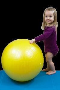 dziecko przy żółtej piłce podczas zajęć fizjoterapeutycznych