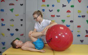 leżące dziecko ze stopami położonymi na czerwonej piłce podczas zajęć fizjoterapeutycznych