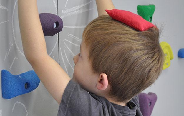 chłopiec z woreczkiem na głowie wykonuje ćwiczenia