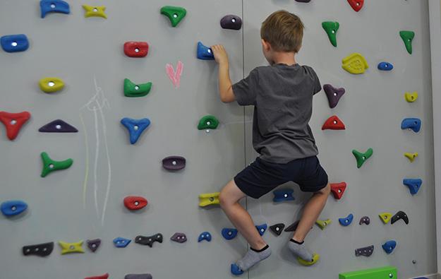 ćwiczenie pośladków na ściance wspinaczkowej. Dziecko stoi przodem na ściance w półprzysiadzie, kończyny dolne w rotacji zewnętrznej.