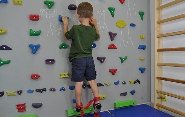 ćwiczenia pośladków na ściance wspinaczkowej. Dziecko stoi wyprostowane przodem na ściance wspinaczkowej. Wokół kostek zawiązana taśma elastyczna.