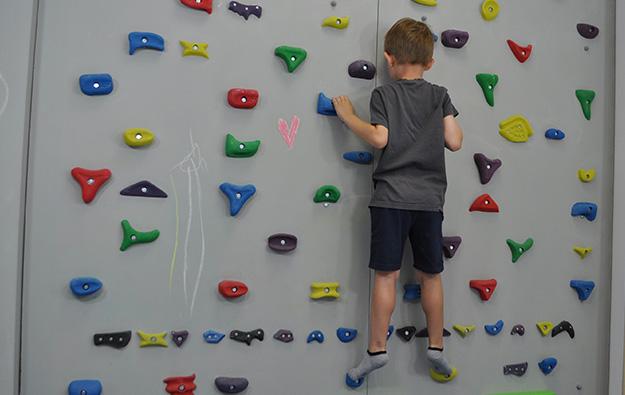 ćwiczenia pośladków na ściance wspinaczkowej. Dziecko stojąc przodem do ścianki w półprzysiadzie i kończynach dolnych w rotacji zewnętrznej, prostuje kolana i napina pośladki.