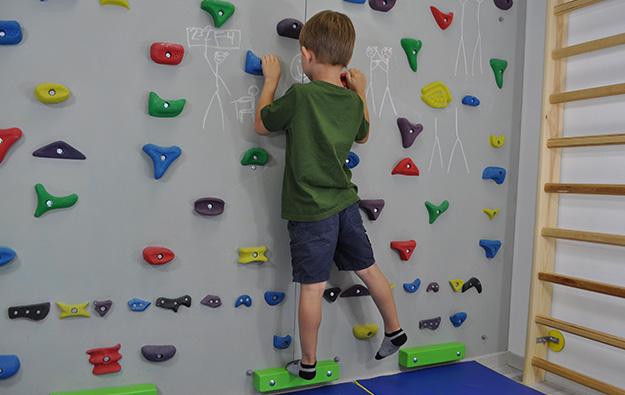 ćwiczenia pośladków na ściance wspinaczkowej. Dziecko stojąc przodem do ścianki wspinaczkowej unosi prostą nogę w bok.