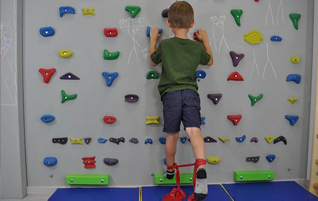 dziecko stoi przodem na ściance, wokół kostek zawiązana taśma elastyczna. Dziecko prostuje nogę w tył napinając taśmę.