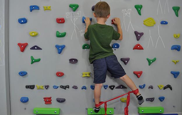 ćwiczenie pośladków na ściance wspinaczkowej. Dziecko stoi przodem na ściance wspinaczkowej, wokół kostek ma zawiązaną taśmę elastyczną . Nogę odwodzi w bok napinając taśmę.
