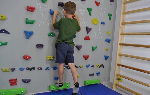 ćwiczenia pośladków na ściance wspinaczkowej. Dziecko stojąc przodem do ścianki prostuje nogę w tył napinając pośladek.