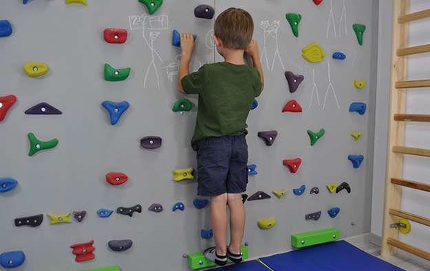 ćwiczenia pośladków na ściance wspinaczkowej. Dziecko stoi wyprostowane przodem do ścianki.