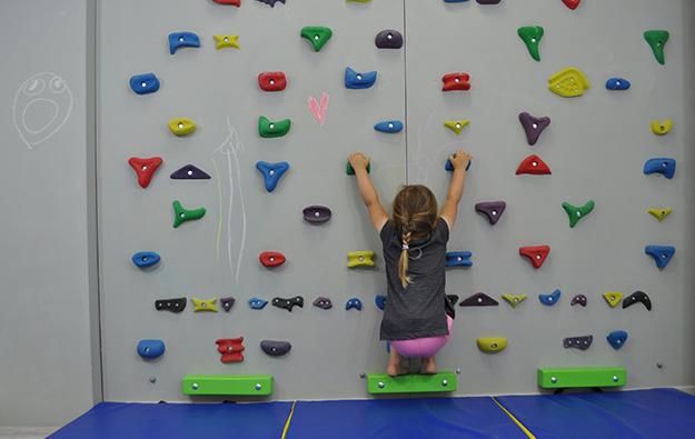 ćwiczenie na odstające łopatki. Dziecko w siadzie skulonym na ściance wspinaczkowej. Kończyny górne wyprostowane w łokciach, równolegle do siebie trzymają chwyty.