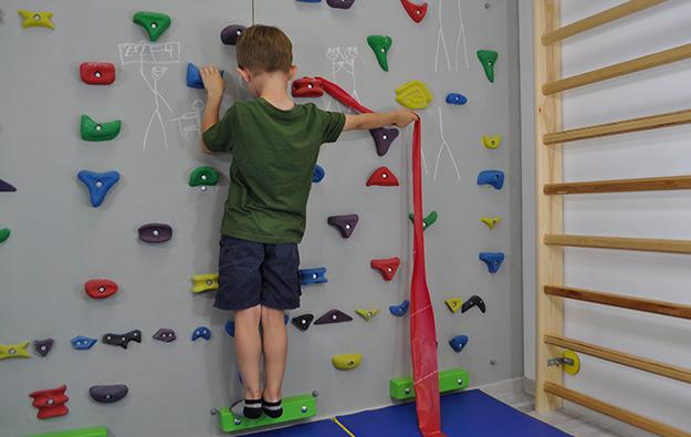 ćwiczenie na odstające łopatki i plecy okrągłe. Dziecko stoi przodem na ściance wspinaczkowej. Lewa kończyna górna zgięta trzyma chwyt. Prawa ręka wyprostowana w łokciu i odwiedziona trzyma taśmę elastyczną przywiązaną do chwytu obok prawej ręki.