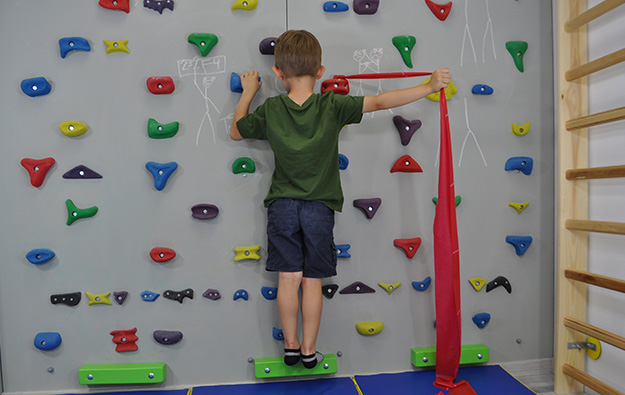 ćwiczenie na odstające łopatki i plecy okrągłe. Dziecko stoi przodem na ściance wspinaczkowej. Lewa kończyna górna zgięta trzyma chwyt. Prawa ręka wyprostowana w łokciu i odwiedziona trzyma taśmę elastyczną przywiązaną do chwytu obok prawej ręki i napina ją.