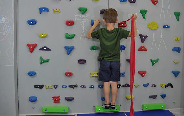ćwiczenie na odstające łopatki i plecy okrągłe. Dziecko stoi przodem na ściance wspinaczkowej. Lewa kończyna górna zgięta trzyma chwyt. Prawa ręka zgięta w łokciu i odwiedziona trzyma taśmę elastyczną przywiązaną do chwytu obok prawej ręki i napina ją w tył.