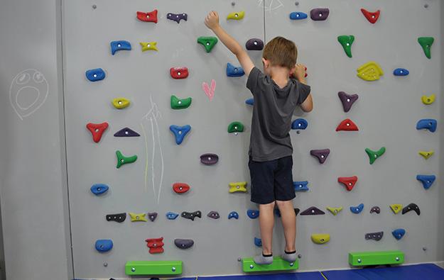 ćwiczenie na odstające łopatki i plecy okrągłe. Dziecko stoi przodem na ściance wspinaczkowej. Nogi złączone. Odrywa lewą rękę w górę i próbuje utrzymać równowagę
