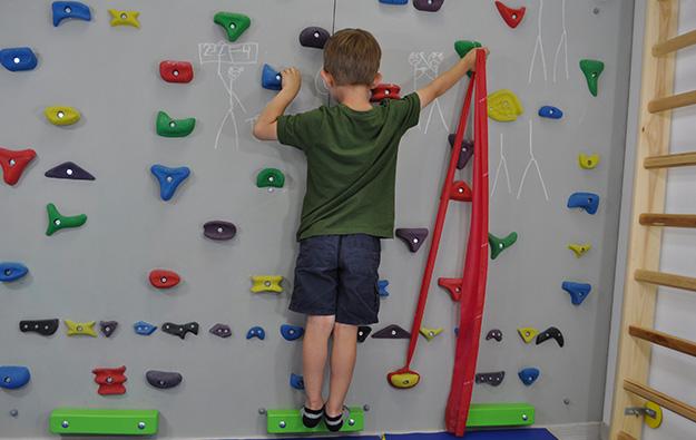 ćwiczenie na odstające łopatki. Dziecko stoi przodem na ściance wspinaczkowej. Lewa kończyna górna zgięta w łokciu oparta na chwycie. Prawa kończyna górna odwiedziona i wyprostowana w stawie łokciowym napina taśmę elastyczną w górę.