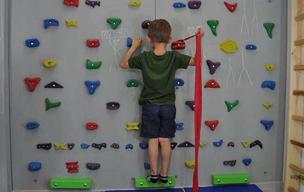 ćwiczenie na odstające łopatki i plecy okrągłe. Dziecko stoi przodem na ściance wspinaczkowej. Lewa kończyna górna zgięta trzyma chwyt. Prawa ręka zgięta w łokciu i odwiedziona trzyma taśmę elastyczną przywiązaną do chwytu obok prawej ręki.