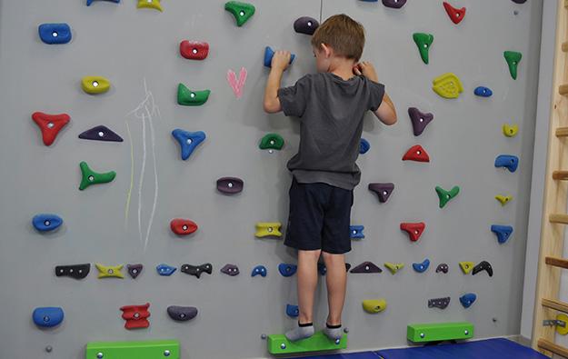 ćwiczenie na odstające łopatki i plecy okrągłe. Dziecko stoi przodem na ściance wspinaczkowej. Kończyny górne zgięte trzymają chwyty.