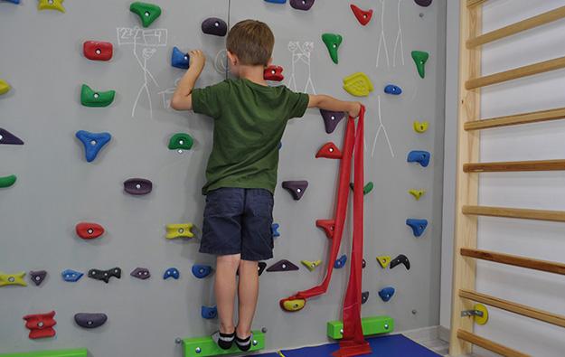 ćwiczenie na odstające łopatki. Dziecko stoi przodem na ściance wspinaczkowej. Lewa kończyna górna zgięta w łokciu oparta na chwycie. Prawa kończyna górna odwiedziona i wyprostowana w stawie łokciowym napina taśmę elastyczną w górę