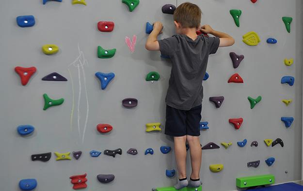 ćwiczenie na odstające łopatki. Dziecko stoi przodem na ściance wspinaczkowej. Kończyny górne wyprostowane w łokciach, równolegle do siebie trzymają chwyty. Dziecko ugina łokcie i przyciąga klatkę piersiową do ścianki.