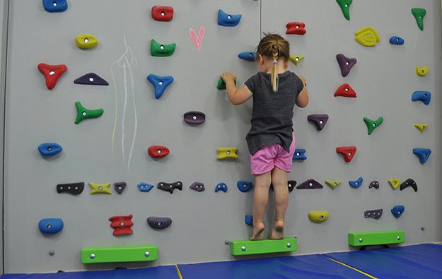 ćwiczenie na odstające łopatki. Dziecko stoi przodem na ściance wspinaczkowej. Kończyny górne wyprostowane w łokciach, równolegle do siebie trzymają chwyty. Dziecko prostuje kolana, ugina łokcie i przyciąga klatkę piersiową do ścianki.
