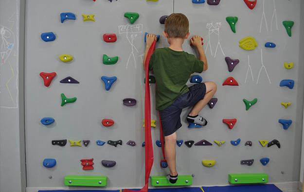 Dziecko stoi przodem na ściance. Lewa noga wyprostowana, prawa zgięta oparta na stopniu. Ręce ugięte w łokciach trzymają chwyty na wysokości klatki piersiowej. W lewej ręce taśma elastyczna, której koniec przywiązany jest do stopnia na wysokości lewej stopy.