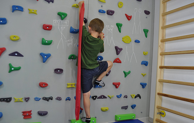 ćwiczenie na skoliozę prawostronną na ściance wspinaczkowej. Dziecko stoi na lewej nodze, prawa zgięta oparta na stopniu. Lewa ręka napina taśmę ciągnąc rękę w górę.