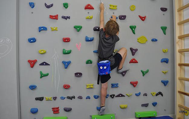 ćwiczenie na skoliozę prawostronną na ściance wspinaczkowej. Dziecko stoi na lewej nodze, prawa zgięta oparta na stopniu. Trzymając kredę w lewej ręce rysuje ciągnąc lewą rękę wysoko w górę. Prawa ręka zgięta trzyma chwyt.