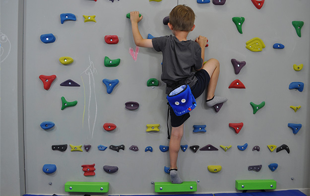 ćwiczenie na skoliozę na ściance wspinaczkowej. Dziecko stoi przodem na ściance. Lewa noga wyprostowana, prawa zgięta oparta na stopniu. Ręce ugięte w łokciach trzymają chwyty na wysokości klatki piersiowej