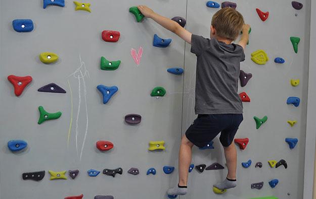 ćwiczenie pośladków na ściance wspinaczkowej. Dziecko stojąc przodem do ścianki w półprzysiadzie prostuje kolana i napina pośladki.