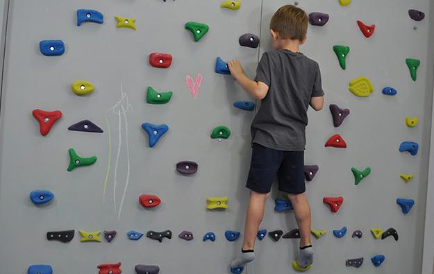 ćwiczenie pośladków na ściance wspinaczkowej. Dziecko stojąc przodem do ścianki z wyprostowanymi kolanami.