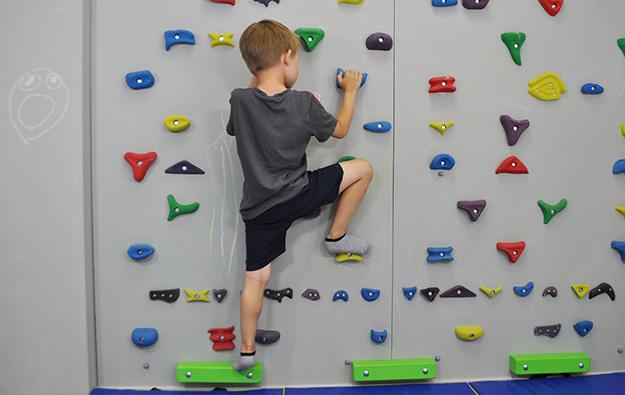 ćwiczenia na stopy chód stopami do środka. Dziecko stoi na ściance wspinaczkowej, stopy zrotowane na zewnątrz, zgina prawą nogę i kładzie na stopniu