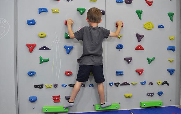 ćwiczenia na chód stopami do środka. Dziecko stoi na ściance wspinaczkowej stopy skręcone na zewnątrz