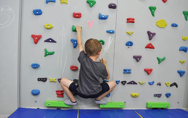 ćwiczenia na stopy chód stopami do środka. Dziecko stoi na ściance wspinaczkowej, stopy zrotowane na zewnątrz, przechodzi do przysiadu z szeroko rozstawionymi nogami i stopami na zewnątrz