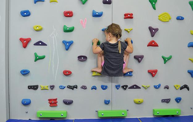 ćwiczenia na chód stopami do środka. Dziecko w przysiadzie z szeroko rozstawionymi nogami stoi na ściance wspinaczkowej