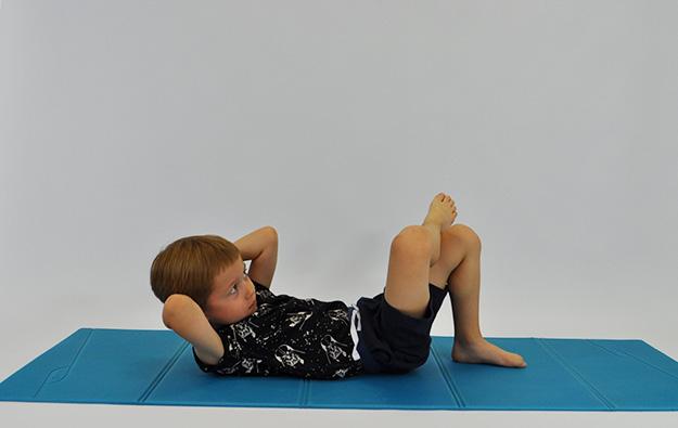 dziecko w leżeniu tyłem zgina tułów ciągnąc łokieć do przeciwnego kolana