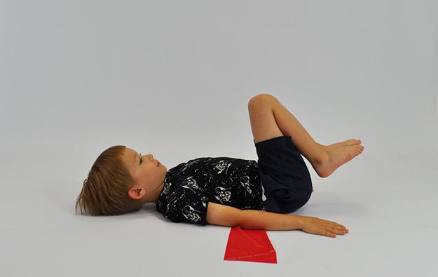 ćwiczenia na mięsnie brzucha. Dziecko leży na plecach, nogi ugięte, stopy na podłodze, pod odcinkiem lędźwiowym taśma elastyczna. Dziecko odrywa nogi i przyciąga je do brzucha rodzic pociąga za taśmę próbując ją wydostać
