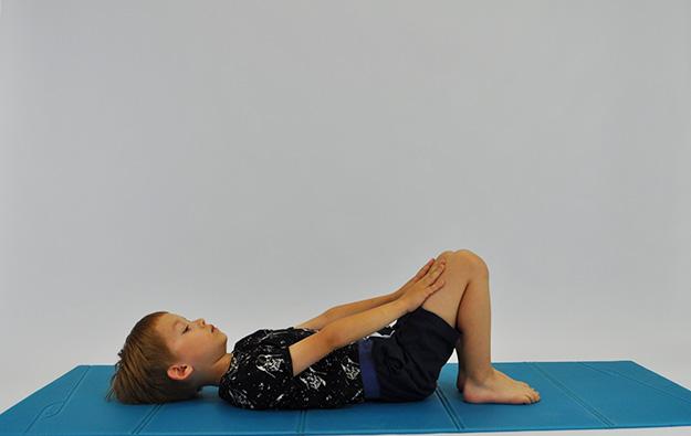 ćwiczenia na mięsnie brzucha. Dziecko leży na plecach, kolana ugięte, stopy oparte na podłodze, dłonie na kolanach