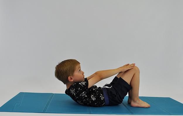 dziecko w leżeniu tyłem zgina tułów, ręce przesuwa w kierunku kolan