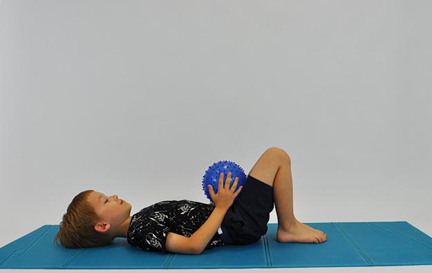 ćwiczenia na mięsnie brzucha. Dziecko leży na plecach, kolana ugięte, stopy oparte na podłodze, dłonie z piłką na kolanach