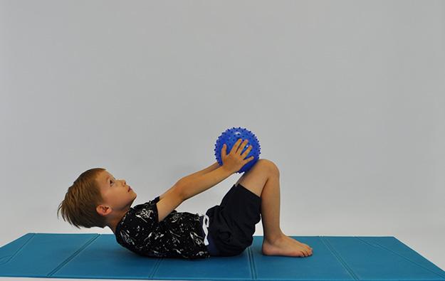dziecko w leżeniu tyłem zgina tułów, ręce z piłką przesuwa w kierunku kolan