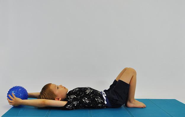ćwiczenia na mięsnie brzucha. Dziecko leży na plecach, kolana ugięte, stopy oparte na podłodze, kończyny górne zgięte w stawach barkowych w dłoniach piłka