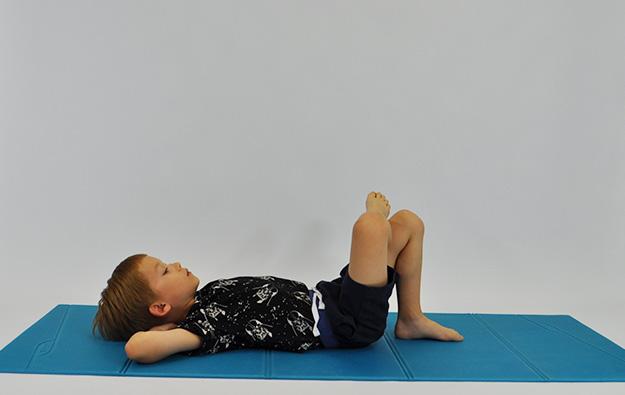 ćwiczenia na mięśnie brzucha. Dziecko leży na plecach, ręce na karku, stopa spoczywa na kolanie jak na zdjęciu