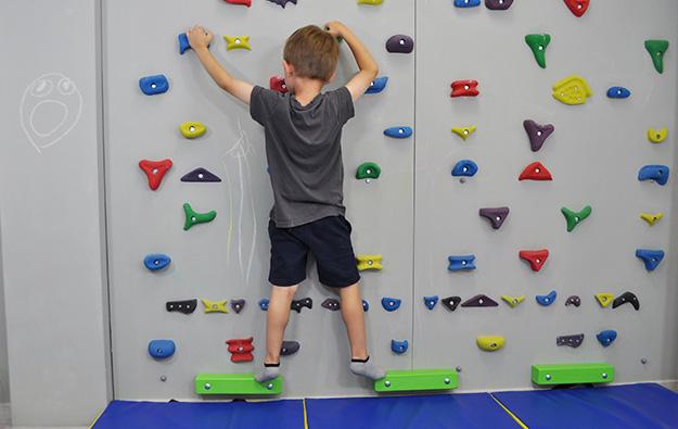 : ćwiczenia na stopy płasko-koslawe. Dziecko stojąc na ściance wspinaczkowej idzie bokiem krokiem dostawnym w poprzek ścianki.