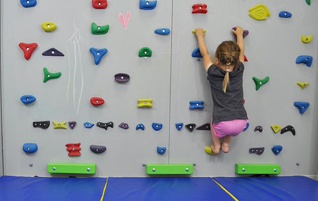 ćwiczenia na stopy płasko-koślawe na ściance wspinaczkowej. Dziecko w przysiadzie na ściance wspinaczkowej.