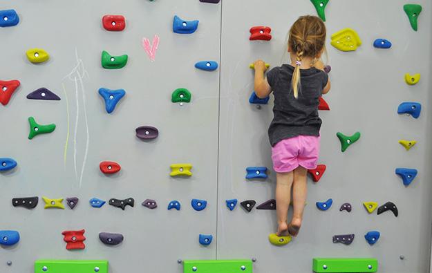 ćwiczenia na stopy płasko-koślawe na ściance wspinaczkowej. Dziecko w przysiadzie na ściance wspinaczkowej przechodzi z przysiadu do wyprostu kolan i wspięcia na palce