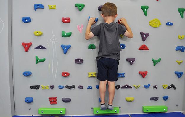 ćwiczenia na stopy płasko-koślawe na ściance wspinaczkowej. Dziecko stoi na ściance wspinaczkowej.