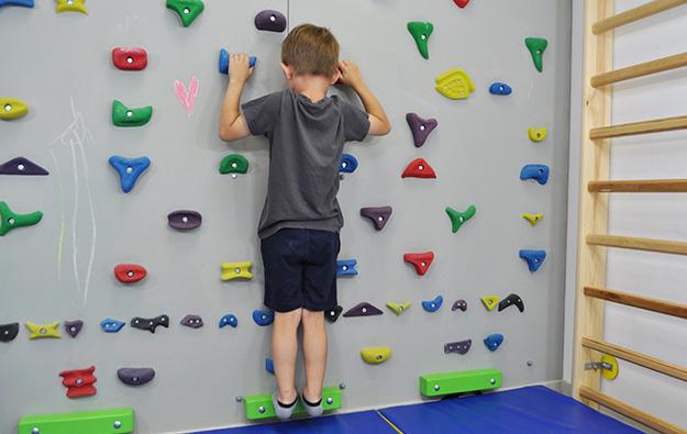 : ćwiczenia na stopy płasko-koslawe. Dziecko stojąc na ściance na palcach, schodzi piętami nisko w dół rozciągając łydki