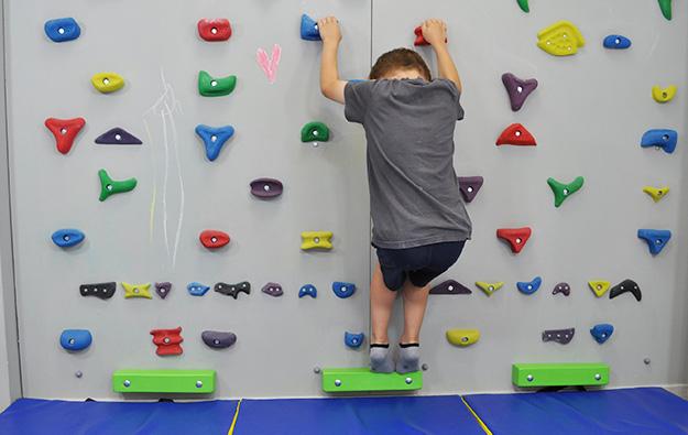 ćwiczenia na stopy płasko-koślawe na ściance wspinaczkowej. Dziecko stoi na ściance wspinaczkowej na palcach w półprzysiadzie