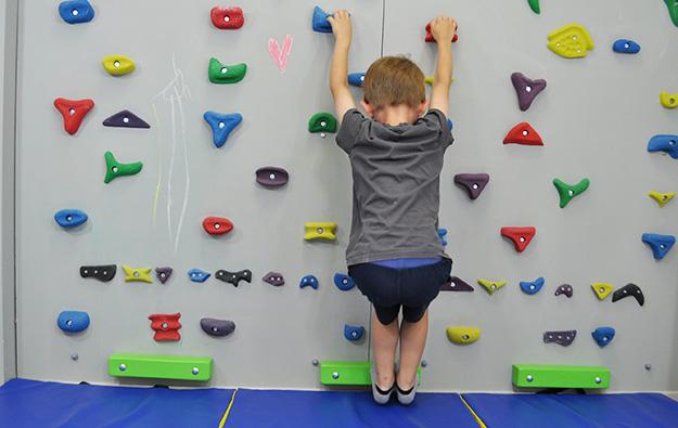 ćwiczenia na stopy płasko-koslawe. Dziecko stojąc na ściance na palcach, schodzi piętami nisko w dół rozciągając łydki