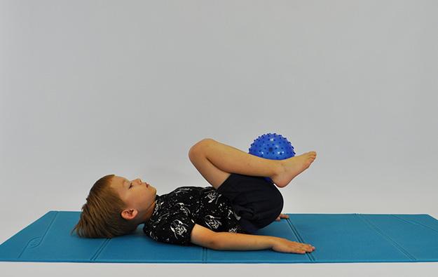 dziecko w leżeniu tyłem trzymając między stopami piłkę, odrywa stopy i kolana przyciąga do klatki piersiowej