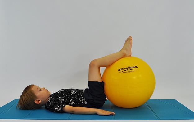 : ćwiczenia na mięsnie brzucha. Dziecko leży na plecach, kolana ugięte, stopy oparte na dużej piłce